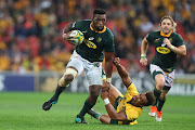 Siya Kolisi of the Springboks breaks through a tackle by Will Genia of the Wallabies during The Rugby Championship match between the Australian Wallabies and the South Africa Springboks at Suncorp Stadium on September 8, 2018 in Brisbane, Australia.
