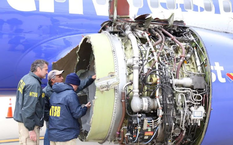 Investigators examine damage to the engine of the Southwest Airlines plane.