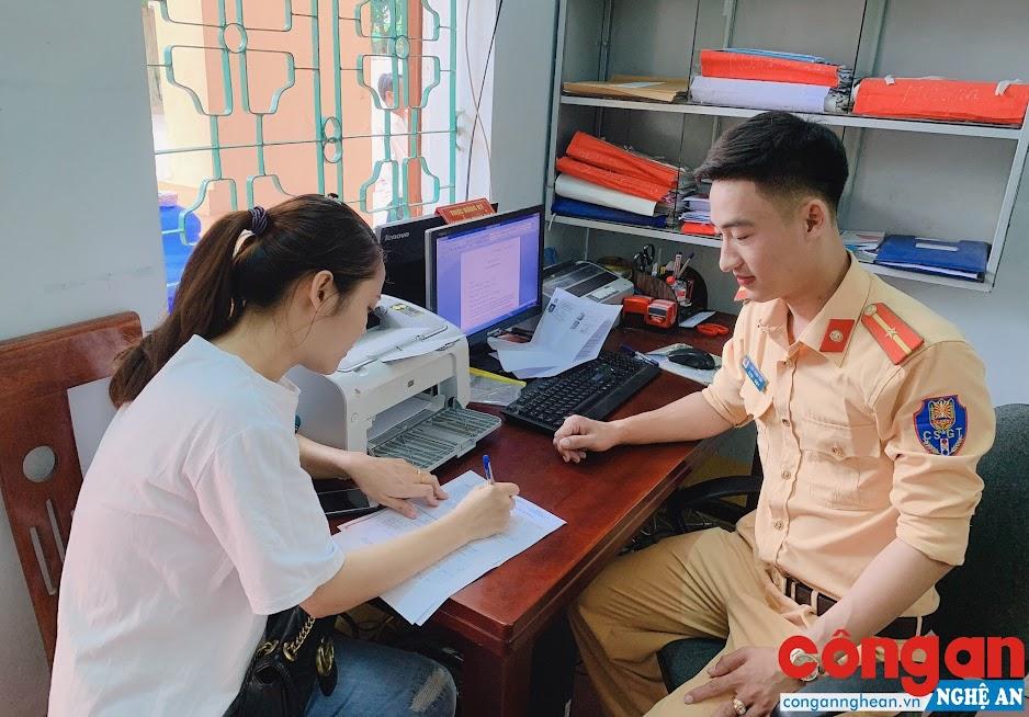 Cán bộ CSGT hướng dẫn người dân làm thủ tục đăng ký phương tiện