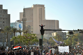 Photo: A man sits atop a light post in Tahrir Square.