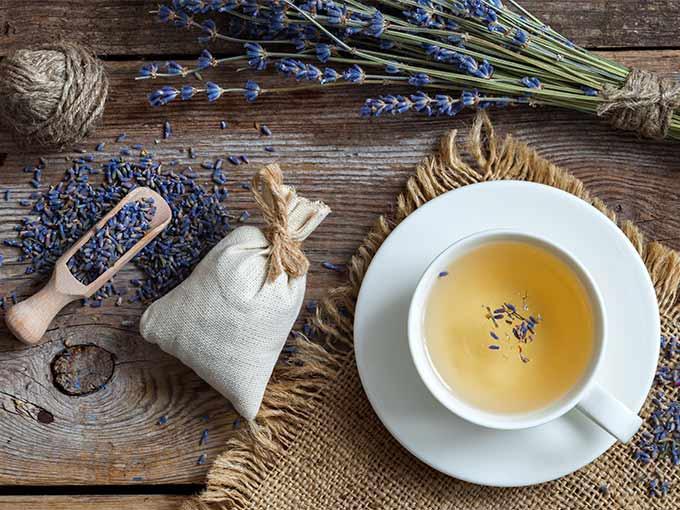 Blutdrucksenkender Tee aus Lavendel in einer Tasse auf einem Holztisch neben Lavendelblüten.