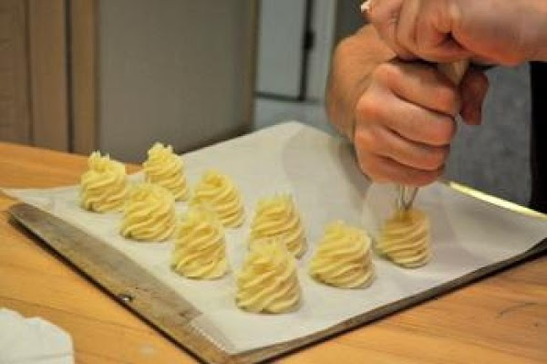 Once the potatoes are mashed, place them in a pastry bag and squeeze onto...