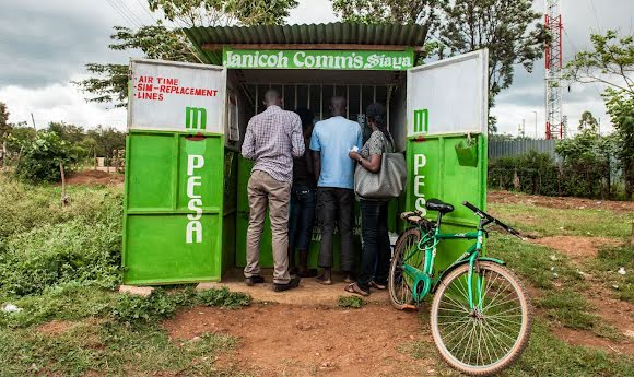 Three people at a mobile device maintenance kiosk, where their phone-based credit can be exchanged for cash.