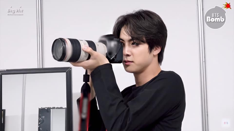 World wide handsome BTS Jin holding camera with