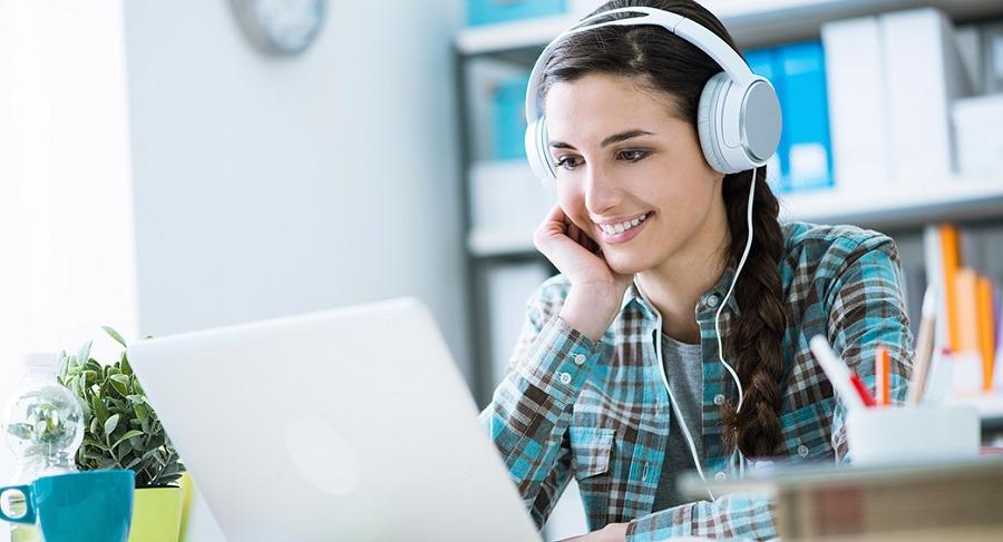 หญิงสาวสวมหูฟังและมองไปที่คอมพิวเตอร์