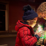 Two children wearing coats holding and looking into a glowing mystical jar