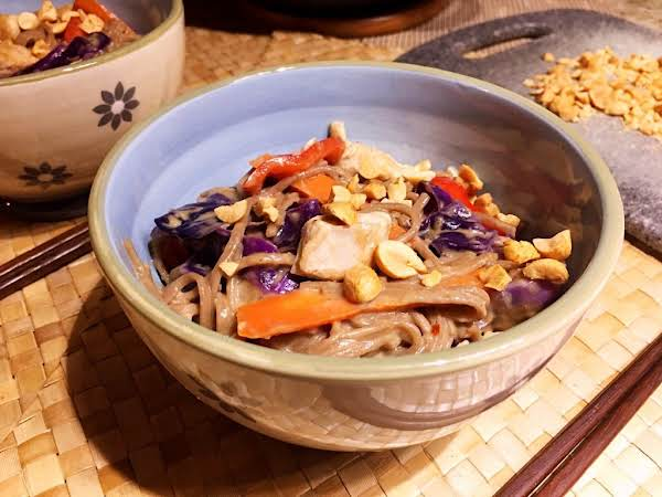 A Bowl Of Soba Noodles Mixed With Red Cabbage, Carrots And Sprinkled On With Peanuts.