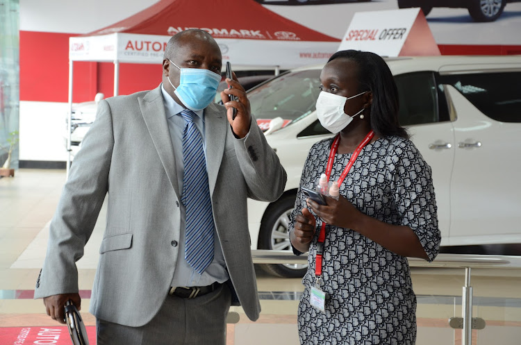 Co-op Bank bank assurance head Joram Kiuna and Toyota Kenya marketing coordinator Angela Mwangi