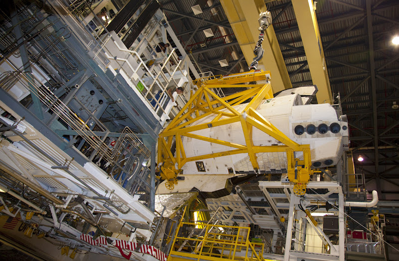 Photo: At NASA's Kennedy Space Center a crane carries an orbital maneuvering system pod closer to space shuttle Discovery, on October 13, 2011. The OMS pod was returned from White Sands Space Harbor in New Mexico where it underwent a complete deservicing and cleaning. (NASA/Frankie Martin) - Via In Focus: http://theatln.tc/GXlgMp