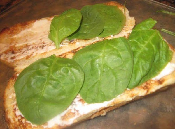 Slather a small amount of mayo on the bread so the spinach leaves have...