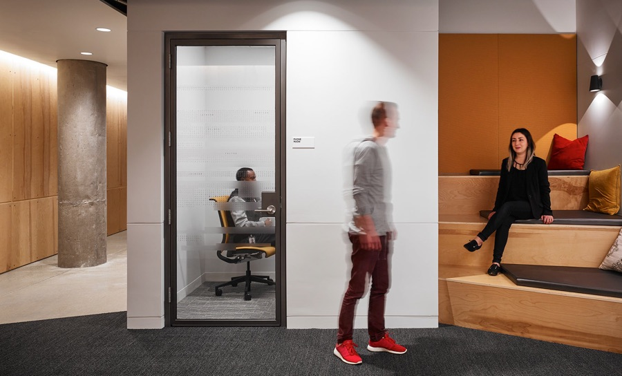A young man passes by another young man in a conference room behind a closed door while greeting a young woman on light wooden stairs