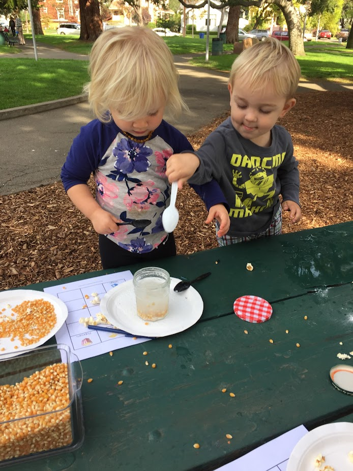 Two toddlers playing at a picnic table