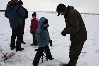 Photo: Risto Ryynänen avittaa kalan irroittamisessa