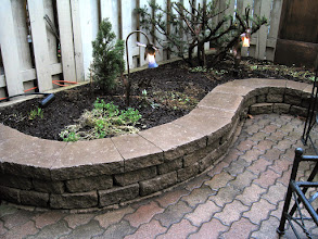 Photo: Reusing the original stone and blending it with a new raised garden wall made this small yard much more usable. Reusing stone doesn't save much money since it needs to be lifted and cleaned BUT it's more eco-friendly since it keeps waste out of the landfill.
