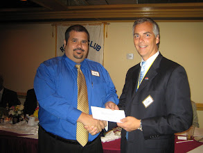 Photo: YMCA Executive Jose Rodriguez (and a member of our club) receives check from President Joe