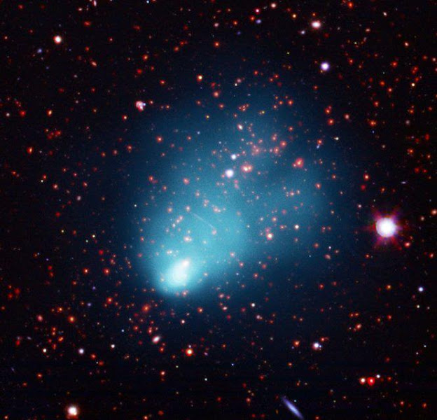 """Photo: El Gordo Galaxy Cluster  A composite image shows El Gordo in X-ray light from NASA's Chandra X-ray Observatory in blue, along with optical data from the European Southern Observatory's Very Large Telescope (VLT) in red, green, and blue, and infrared emission from the NASA's Spitzer Space Telescope in red and orange.  X-ray data from Chandra reveal a distinct cometary appearance of El Gordo, including two """"tails"""" extending to the upper right of the image. Along with the VLT's optical data, this shows that El Gordo is, in fact, the site of two galaxy clusters running into one another at several million miles per hour. This and other characteristics make El Gordo akin to the well-known object called the Bullet Cluster, which is located almost 4 billion light years closer to Earth.  As with the Bullet Cluster, there is evidence that normal matter, mainly composed of hot, X-ray bright gas, has been wrenched apart from the dark matter in El Gordo. The hot gas in each cluster was slowed down"""