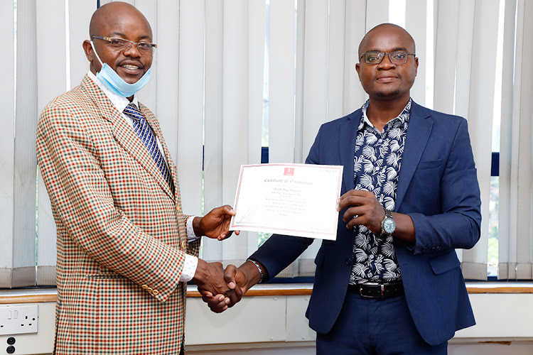 Matungu constituency Roots Party of Kenya nominee Noah Shiunzi receives his certificate from party logistics director Paul Omolo at Lion Place, Westlands, Nairobi, on December 23, 2020 .