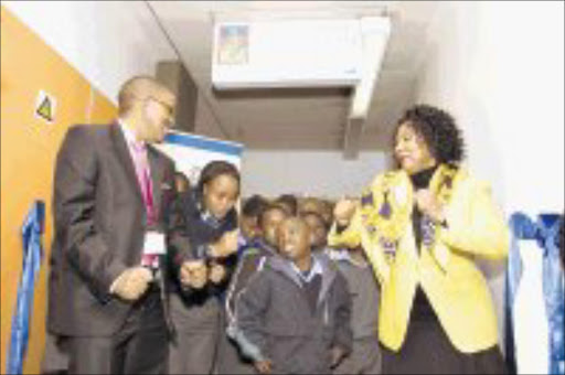DANCING TIME: Medscheme chairman Obakeng Mooketsi (left) and Department of Health deputy director general Anna Mokgokong, dance with pupils at the official unveiling of the newly refurbished Johannesburg Hospital School. © Unknown.