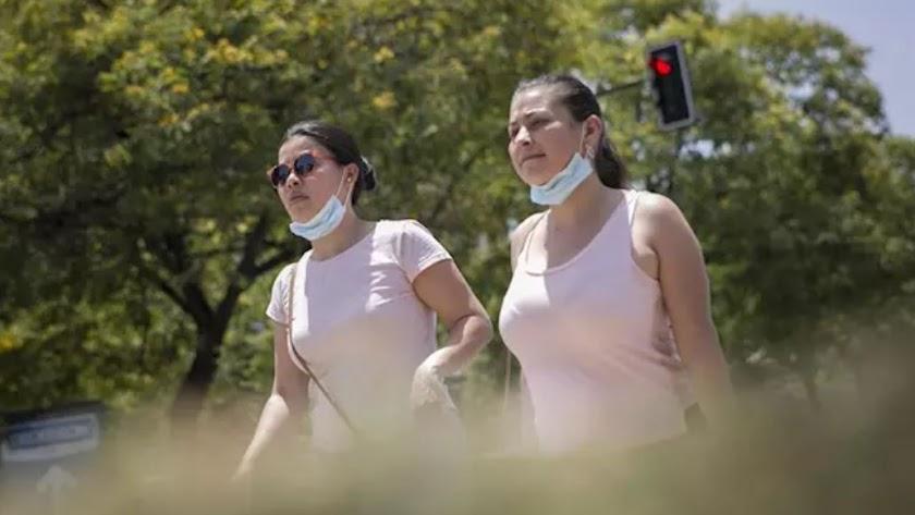 Dos mujeres caminan con la mascarilla bajada.
