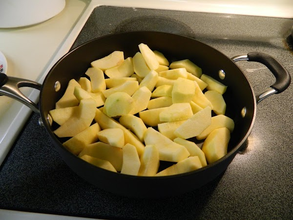 Slice butter in bottom of a 12' skillet. Peel, core and quarter apples, add to...