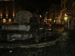 """Photo: La fontaine représente un homme, livre à la main, qui se repose sur le bord d'une fontaine tandis qu'un chien joue à mordiller sa manchette gauche. Cet homme, c'est Charles Buls, orfèvre dans cette rue du Marché aux Herbes, comme son perre masi qui s'impliqua aussi dans la vie politique. Il fut bougmestre de la Ville de Bruxelles de 1881 à 1899. La frise en bronze qui couronne la fontaine énumète quelques étapes de ses voyages en Italie et en Grèce, compléments à sa formation artistique. Sous son maïorat, la ville entrepris la restauration de son patrimoine comme le soulingne,nt les sculptures de l'hôtel de ville et de la porte de Hal sur la frise de la fontaine. Le bassin de la fontaine est du type """"agora"""""""