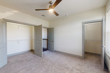Bedroom with carpet, light walls, and ceiling fan