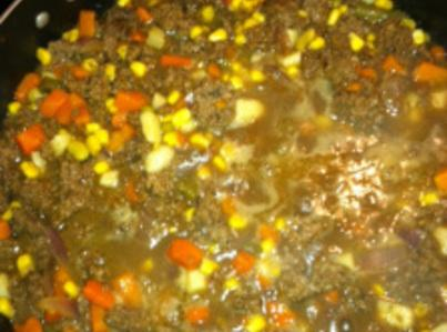 After the ground chuck beef and onion are browned and drained, add the four...