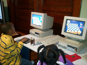 Photo: both of them on the computers. Kaleya learning moves and Jihad playing a game