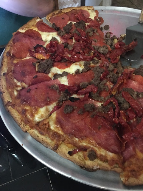 Meat lovers delight with sun dried tomatoes on top.