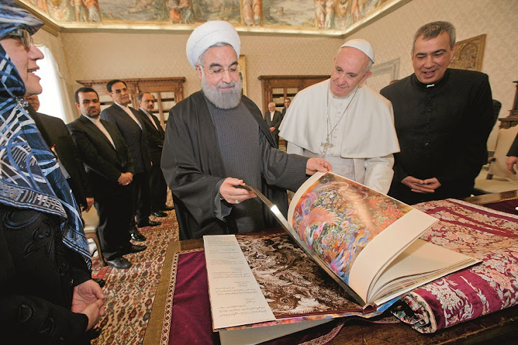 NEW ALLY: Pope Francis and Iranian president Hassan Rouhani exchange gifts during a meeting at the Vatican. Italy and Iran earlier signed business deals worth $18.4bn during Rouhani's visit to Italy, which is aimed at rebuilding ties with the West after sanctions imposed on Iran were formally lifted this month. Picture: GALLO IMAGES/AFP/XAVIER LEOTY