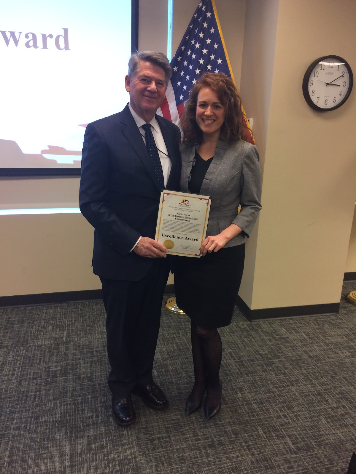 On behalf of the Eastern Shore Land Conservancy, Katie Parks accepts the Award of Excellence from Maryland Department of Housing and Community Development Secretary Kenneth Holt.