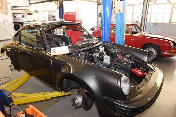 The workshop floor is also a hospital where they rebuild classic Porsches for clients. Picture: FREDDY MAVHUNDA