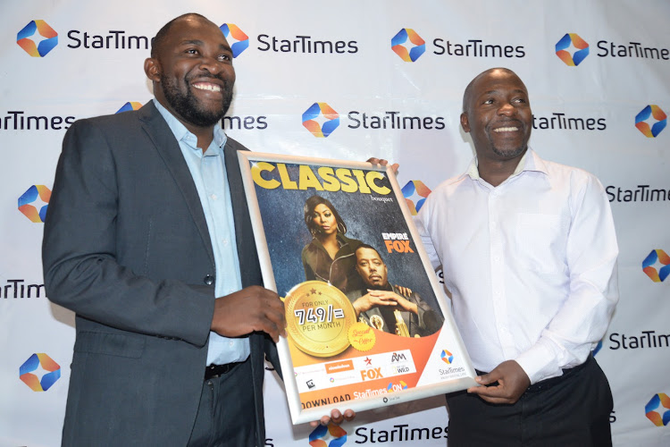 StarTimes marketing director Japhet Akhulia (left) is joined by regional director marketing Aldrine Nsubuga (Right). The company has extended a 50 per cent price cut on the bouquet to grow subscriber base.
