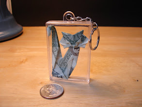Photo: Model: Gato (Cat);  In a plastic box with a chain and keyring attached;  Creator: Roman Diaz;  Folder: William Sattler;  1 dollar;  Source: Origami Chile http://origami-chile.cl/diagramas/internacionales/gato.html