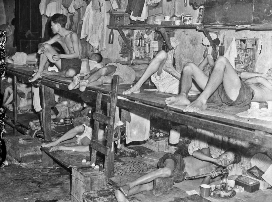 Photo: Photographer: Harrison Forman Singapore, view inside opium den, 1941   Prior to 1943, these dens were legally required to close by 9 pm. However, most smokers would retire to makeshift quarters inside these dens to continue their vice till midnight. The rooms inside were lined with wooden benches. Men in pairs shared a dim lamp between them and smoked leisurely whilst lying on the benches.