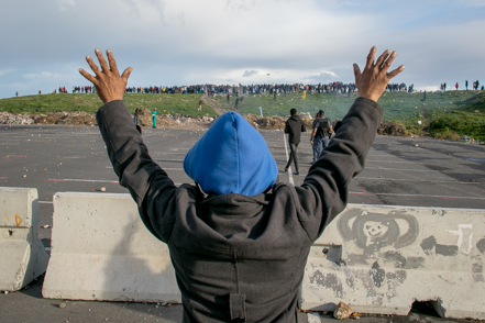 A Hermanus resident holds up his hands in an attempt to stop protesters from throwing rocks at police on Friday.