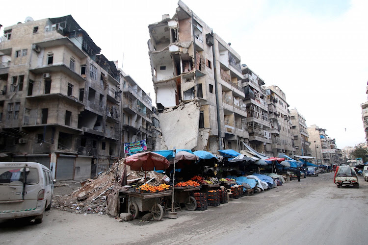Stalls are seen on a street beside damaged buildings in the rebel held al-Shaar neighborhood of Aleppo, Syria. Picture: REUTERS