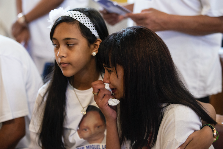 Raylene Louw held by her daughter Mikayla as they say their final goodbye to Miguel Louw at his funeral in Durban.