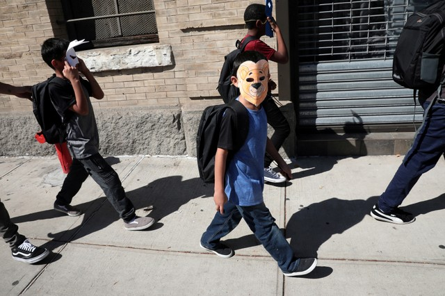 Children, with their faces covered with masks, leave the Cayuga Center, which provides foster care and other services to immigrant children separated from their families, in New York City, US, June 21, 2018.