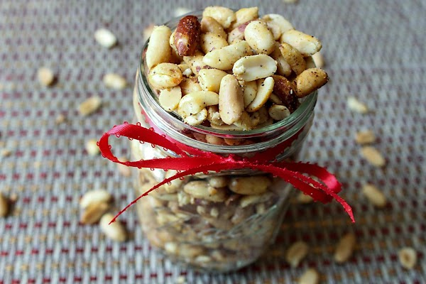 Spicy peanuts in a mason jar with a red ribbon.