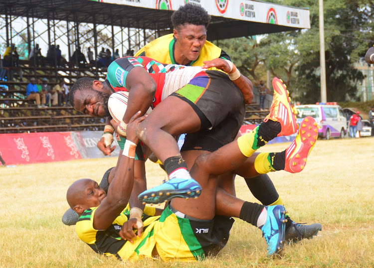 Kabras sugar's Fabian Olando and Mario Wilson tackle Willy Ambaka of Kenya Harlequins during their Kenya Cup clash early this year