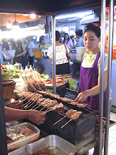 "Photo: vendor grilling ""moo bping"" – marinated pork on skewers – over hot charcoal at Or Tor Kor"