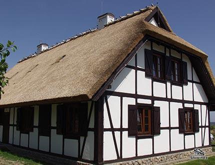 Budynek dwupoziomowy z muru pruskiego z dachem trzcinowym