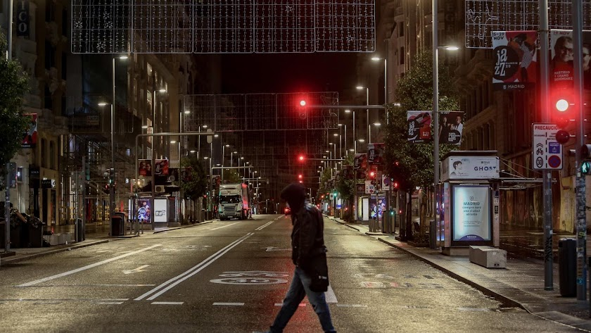 Un chico cruza una calle ante del toque de queda.
