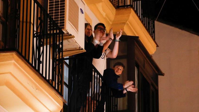 Una familia aplaudiendo ayer desde el balcón, que ha pasado a ser el catalejo desde el que se avizora la poca vida del exterior.
