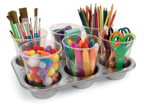 A muffin pan becomes a craft caddy.  Magnets hold the plastic cups down to...