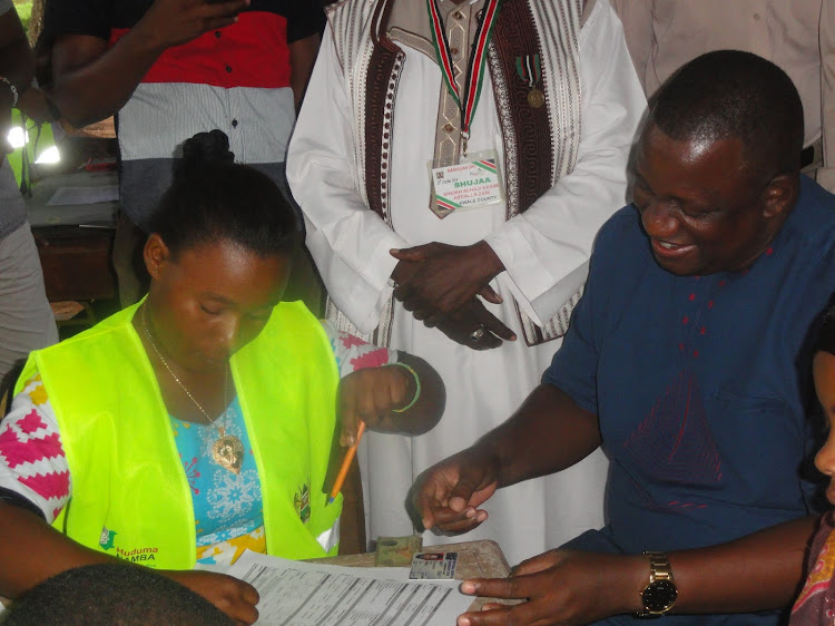 Governor Salim Mvurya goes through Huduma Namba registration process at kwale Baraza Park in Matuga sub-county in 2019.