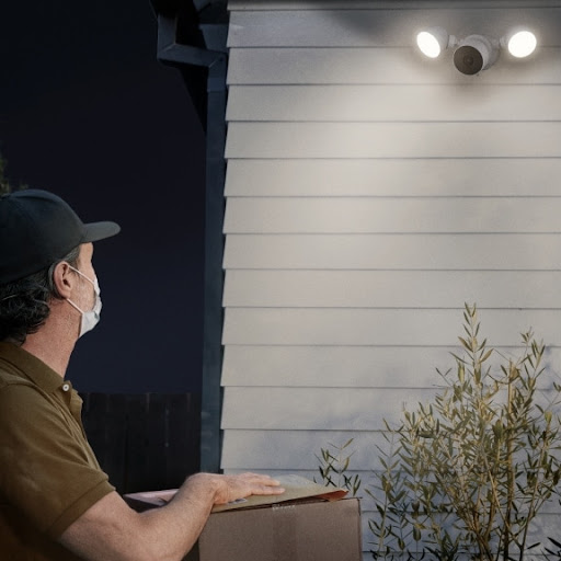 A delivery person approaches a house with a parcel.