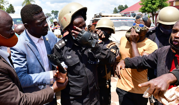 Ugandan pop star and presidential candidate Robert Kyagulanyi, also known as Bobi Wine, assists one of his bodyguards who was injured in clashes between Wine's supporters and security forces in Kayunga district near Kampala on Tuesday.