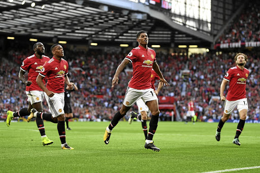 Manchester United forward Marcus Rashford celebrates with teammates after scoring.